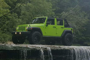 A Jeep Sitting on top of a rock by a waterfall in the river.